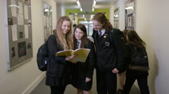 4K Portrait of young girls looking at book in busy school corridor - stock footage