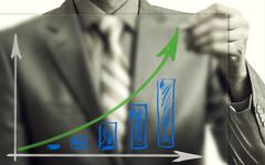 Businessman drawing rising graph, development and growth concept - stock photo