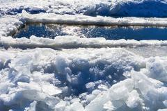 broken ice blocks and ice-hole in frozen rive - stock photo