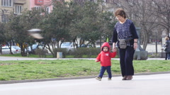 Child walks hand in hand with granny - has recently learned to go Stock Footage