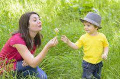 Beautiful young mother playing with her son in grass with dandelions Stock Photos