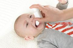 Baby getting medicine through oral spray - stock photo