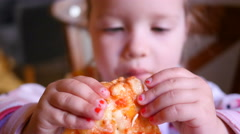 Little kid girl eating tasty pizza at a restaurant table - kid in fast food Stock Footage