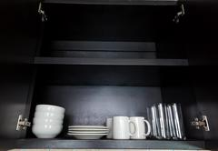 White kitchenware in black cupboard Stock Photos