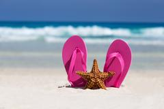 Pink flip flops and starfish on white sandy beach - stock photo