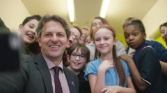 4K Happy teacher & pupils pose for selfie in school hallway Stock Footage