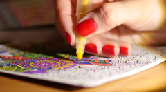 Painting adult coloring book at evening home by reading-lamp light Stock Footage