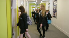 4K Young school children enter classroom for a lesson as teacher waits by door - stock footage