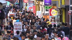 People walk through a busy crowded shopping street in Seoul, South Korea - stock footage