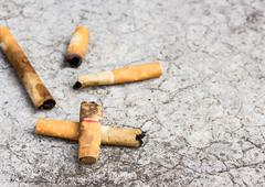 Cigarette butt discarded on the cement floor - stock photo