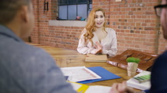 4K Young woman sits opposite business people in a meeting. Stock Footage