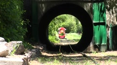 Miniature train rolling through tunnel Stock Footage