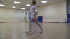 Little girl in white ballet gown funny running around in empty gym. Time Lapse. Stock Footage