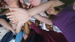 4K Low angle view looking up, happy group of children put their hands together - stock footage