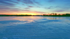 Flying low over scenic frozen river at sunrise Stock Footage