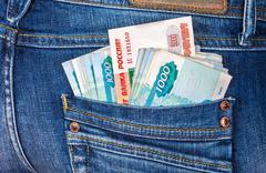 Russian rouble banknotes sticking out of the back jeans pocket - stock photo