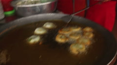 Medium CU woman cooking fritters in a small market in Southeast Asia Stock Footage