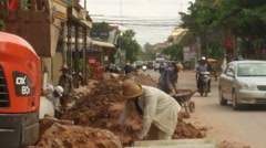 ROADSIDE CONSTRUCTION: An excavator digs a trench near passing traffic - stock footage