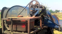 Mechanical rice separator in Asia with female worker nearby Stock Footage