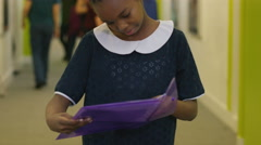 4K Portrait of young girl holding a folder in busy school corridor Stock Footage