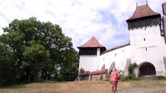Woman approaching the gate tower of a medieval fortress has wanted to visit Stock Footage