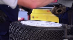 Worker removing rubber wheels on a metal bag at a car workshop Stock Footage