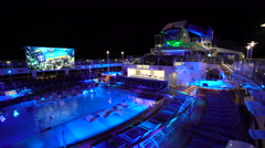 Illuminating cruise ship pool deck at night - Anthem of the seas - stock footage