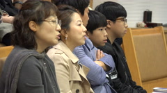 A South Korean family singing during a church mass in Seoul - stock footage