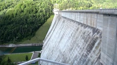 Concrete dam built between two mountain slopes and that close a artificial lake Stock Footage