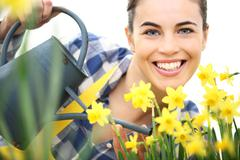 Springtime, smiling woman  in garden with watering can, watering flowers narc Kuvituskuvat