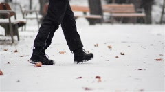 Man with black pants go on a snowy alley from the park Stock Footage