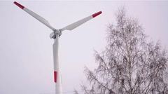 Propeller wind turbines that sit motionless behind a tree Stock Footage