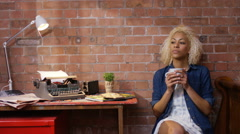 4K Young woman looks thoughtful, sitting at desk with typewriter in home office - stock footage