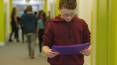 4K Portrait of young boy holding a folder in busy school corridor. - stock footage