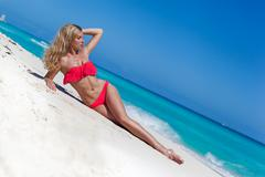 Slim tanning woman with long blond hair lying on tropical beach near  sea - stock photo