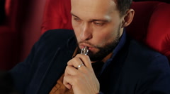 Brutal guy with a beard smokes an electronic cigarette in a red armchair Stock Footage