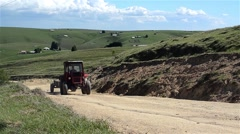 Tractor that pulls a trailer behind him climb on a country road among green Stock Footage