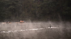 Bamboo rafting through the mist on the lake in morning Stock Footage