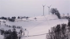 Wind farms built on a hill and covered by drifts of snow - stock footage