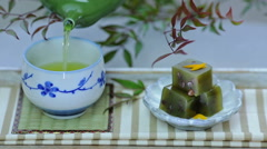 Green tea cup and Japanese sweets (yokan) on table. Stock Footage