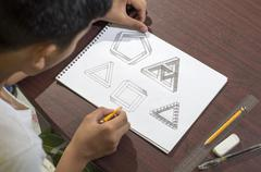 Asian boy learning and practicing to draw 3D shapes - stock photo