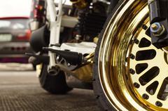 Big motorcycle front wheel, focus shiny golden mag wheel Stock Photos