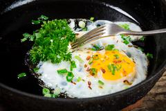 Fried egg with greens in pan Stock Photos
