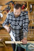 Carpenter sawing wood with hand saw in workshop Stock Photos