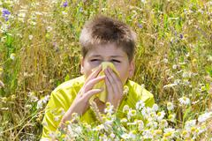 Boy with allergic rhinitis in  meadow - stock photo