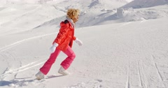Person in snowsuit running up mountain Stock Footage