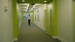 4K Man walking alone through modern school corridor - stock footage