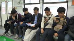 Checking smartphones, commuter train, transport, reading papers, contrast Asia Stock Footage