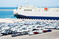 Blurred new cars waiting to export via ship - stock photo