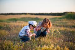 boy girl insect spring grass look point finger sun - stock photo